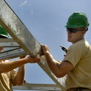 construction workey wearing yellow polo shirt and green safety helmet