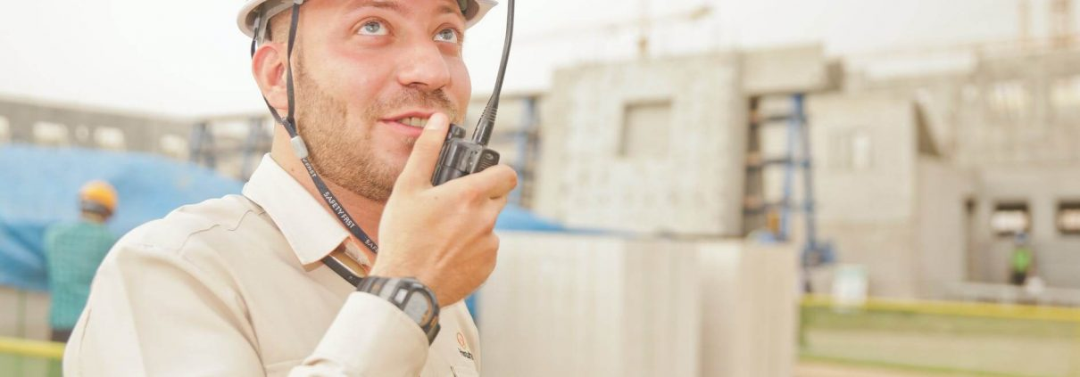man in construction site talking into a walkie talkie